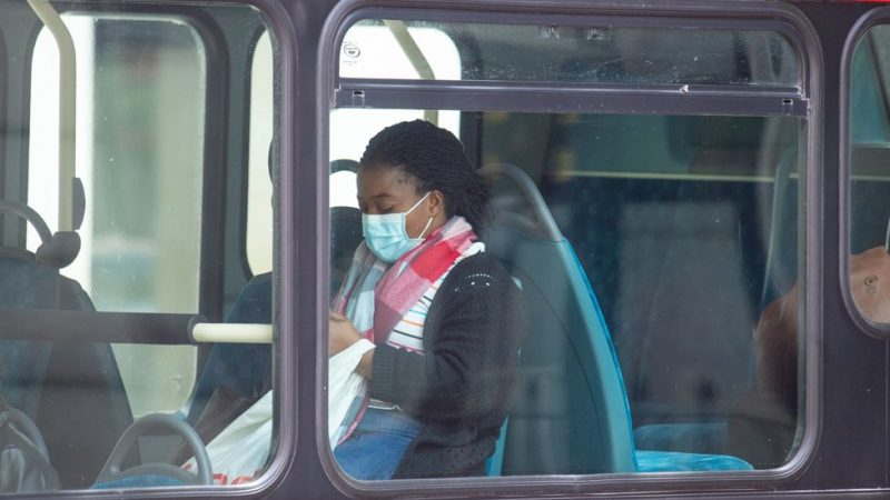 A young Black woman sits in a bus, wearing a mask.